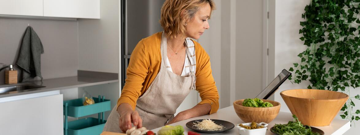 Woman in kitchen, looking at a recipe on a tablet while cooking.