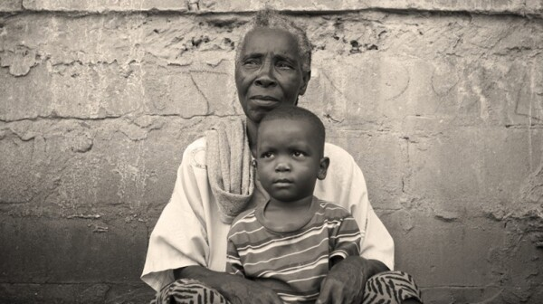 An African grandmother sits with a grandchild.