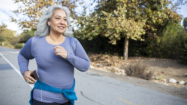 A woman jogging outside on a trail