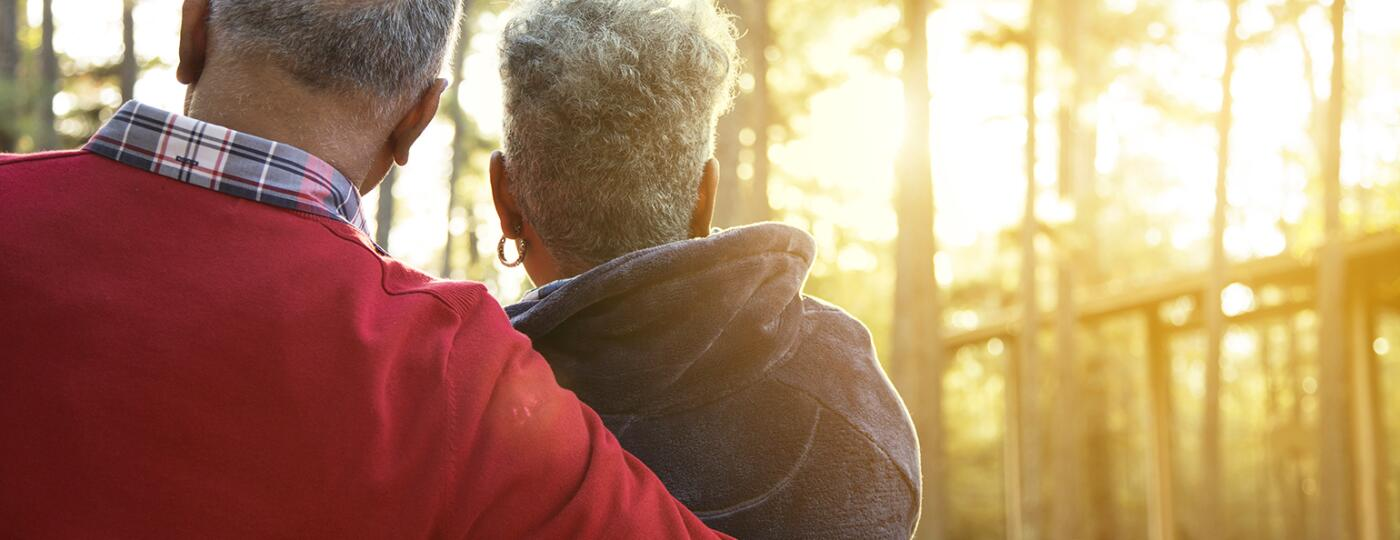 Active senior adult couple enjoy outdoor park at sunset.