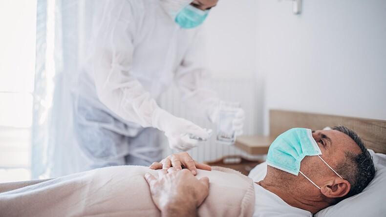 Senior man lying in hospital bed because of coronavirus infection