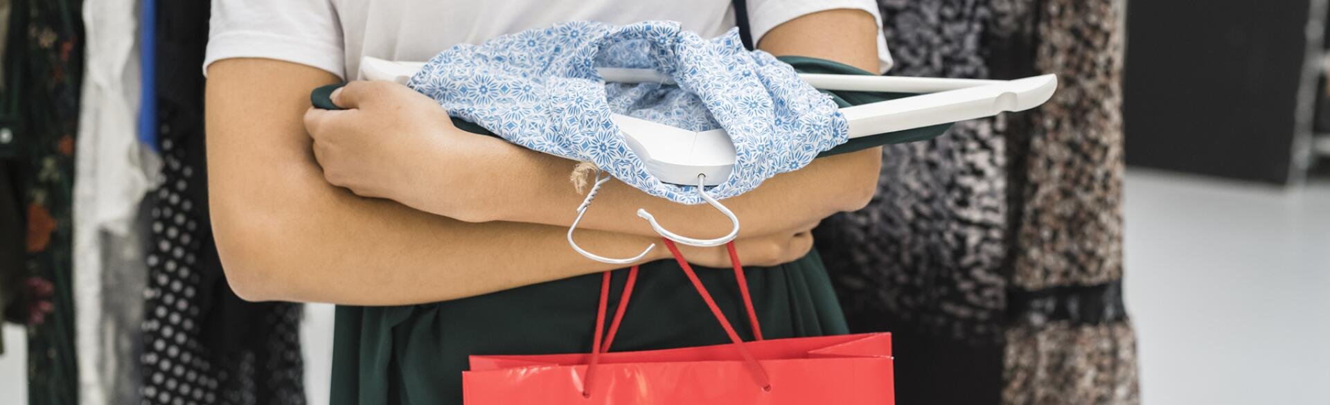 Details Of A Woman Holding Clothes And Bag In A Shop