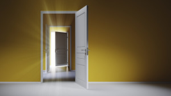 Open white doors with rays of light on blue wall