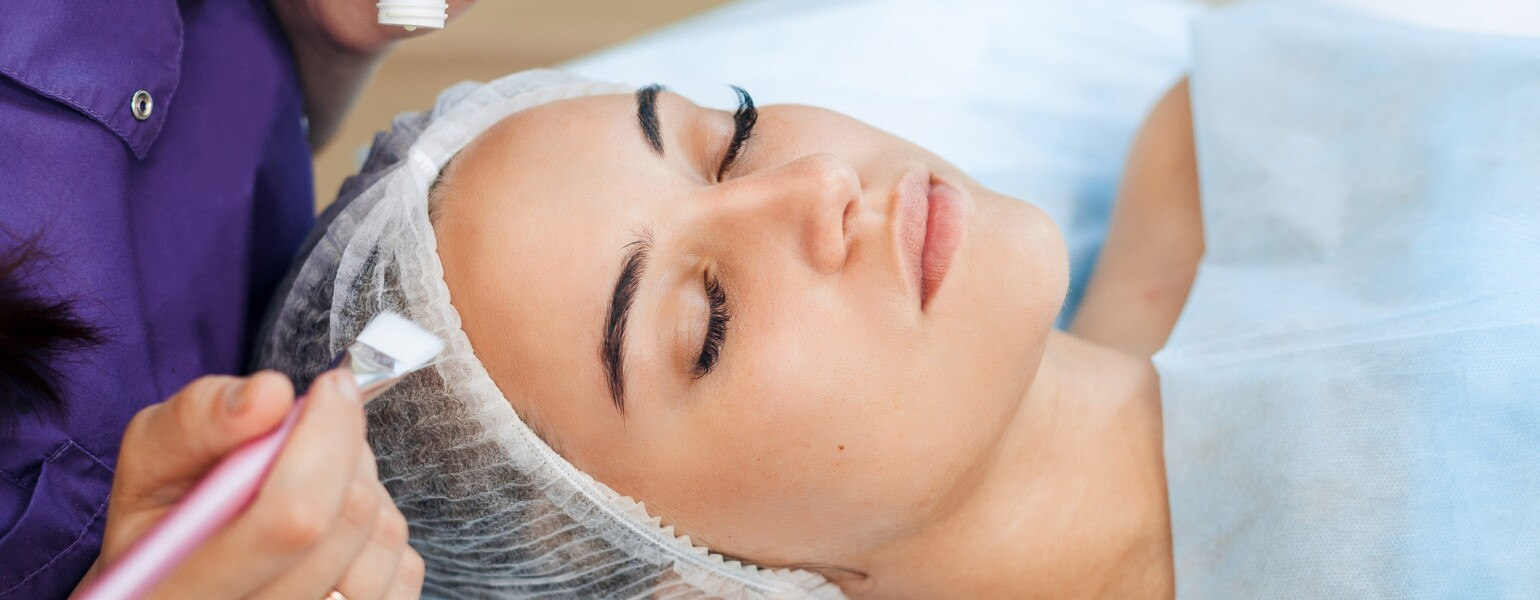 Woman cosmetologist to apply the cream-mask on the face. Cosmetic procedures