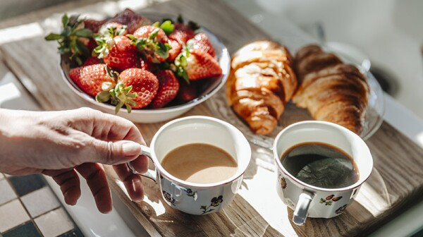 A close-up view of two cups of coffee, strawberries and croissants