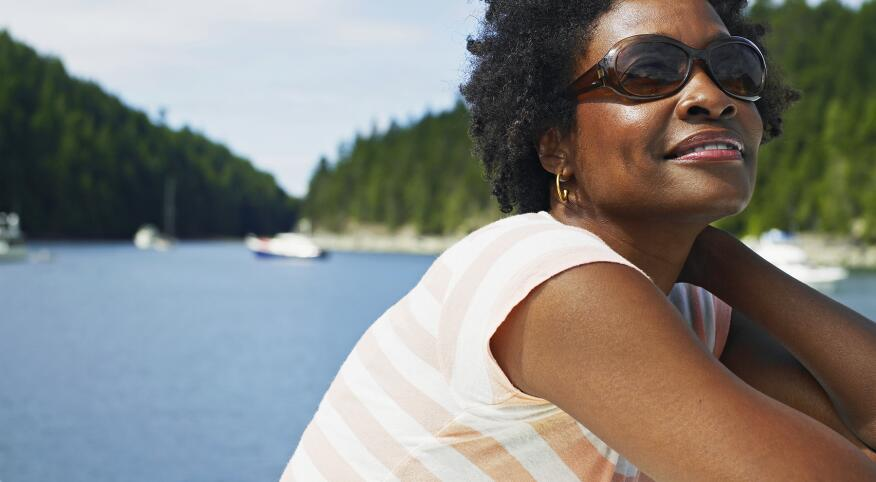 Mature woman in sunglasses sitting on deck of yacht,smiling