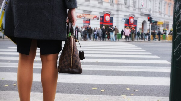 Woman holding designer bag waiting at intersection