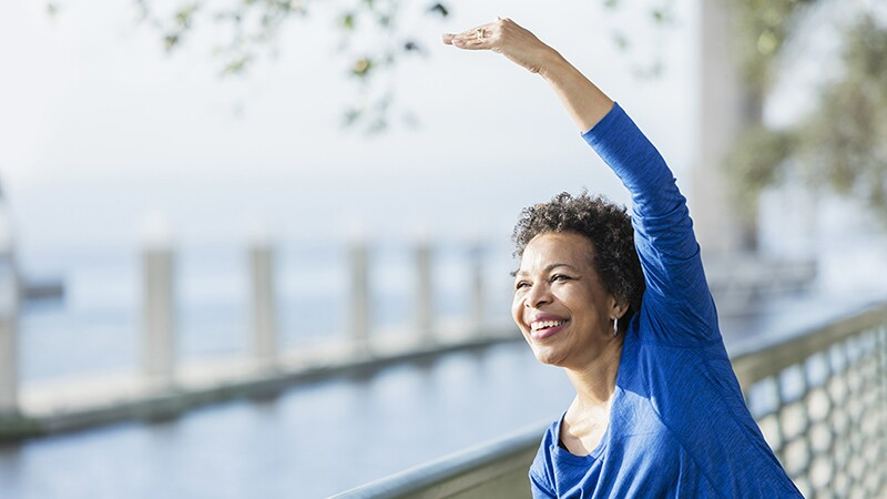 A woman stretching her arm over her head along a waterfront