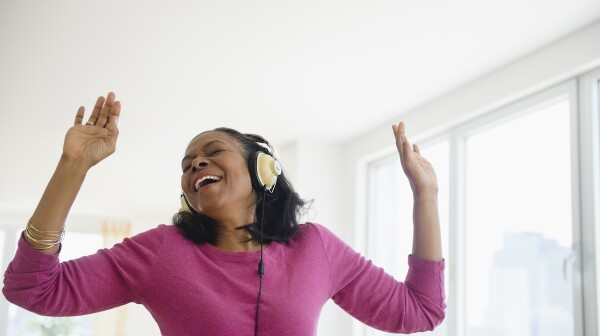 African American woman wearing headphones dancing.