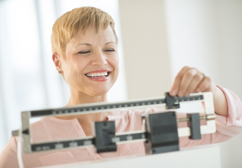 Happy Woman Adjusting Balance Weight Scale