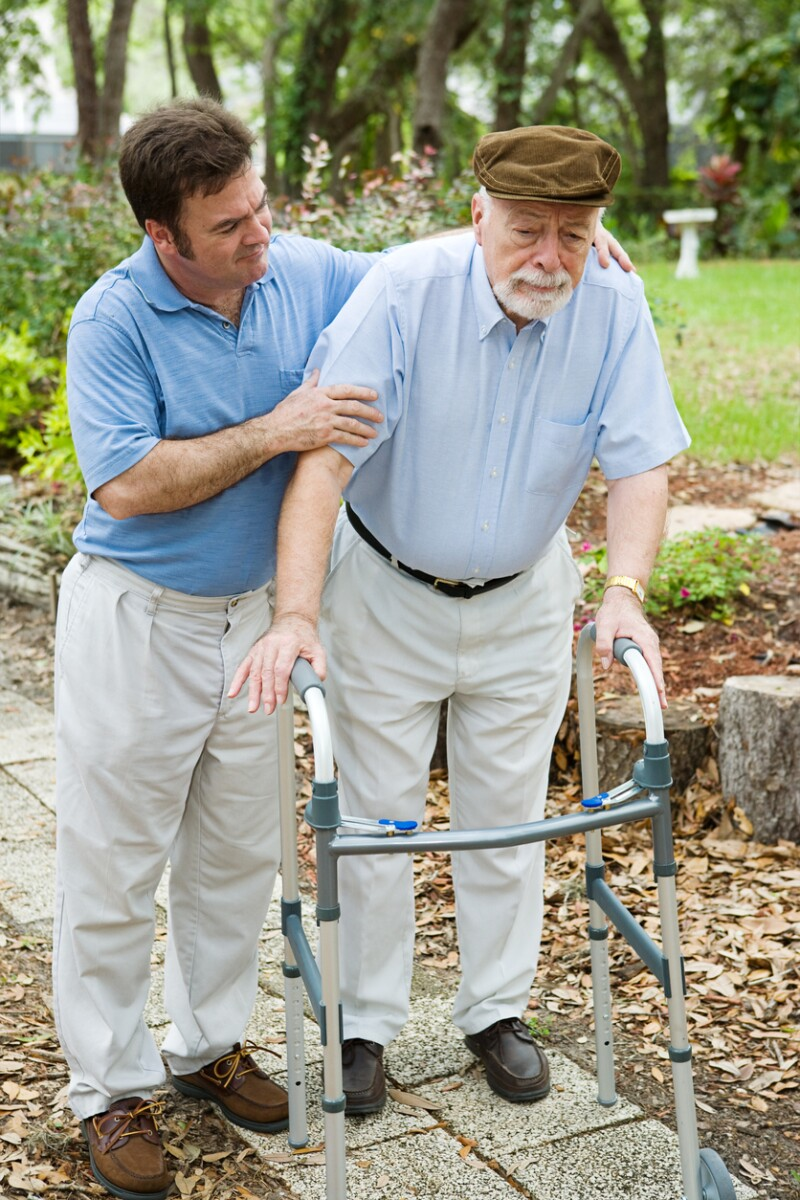 A man helping his elderly father walk