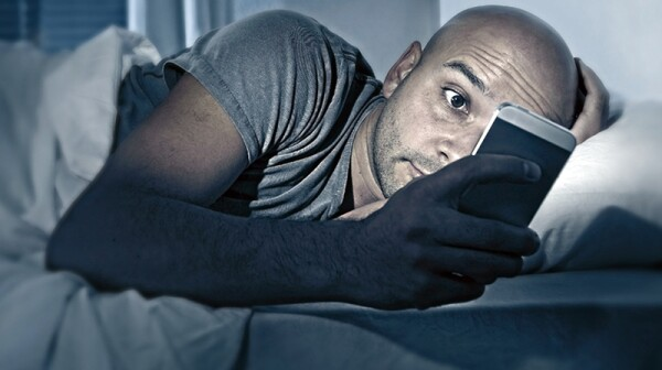 A man looking at his phone while in bed