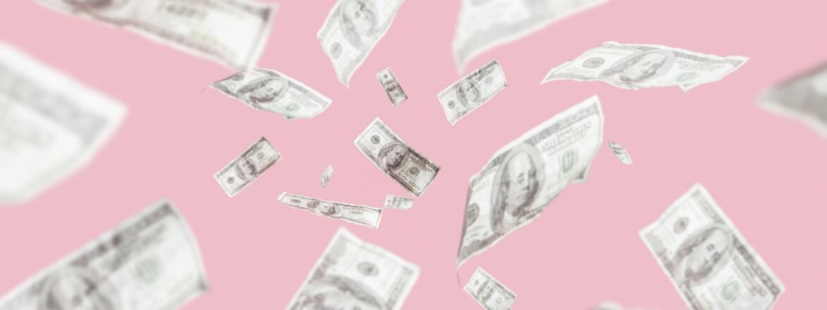 Money on a pink backdrop floating in the air
