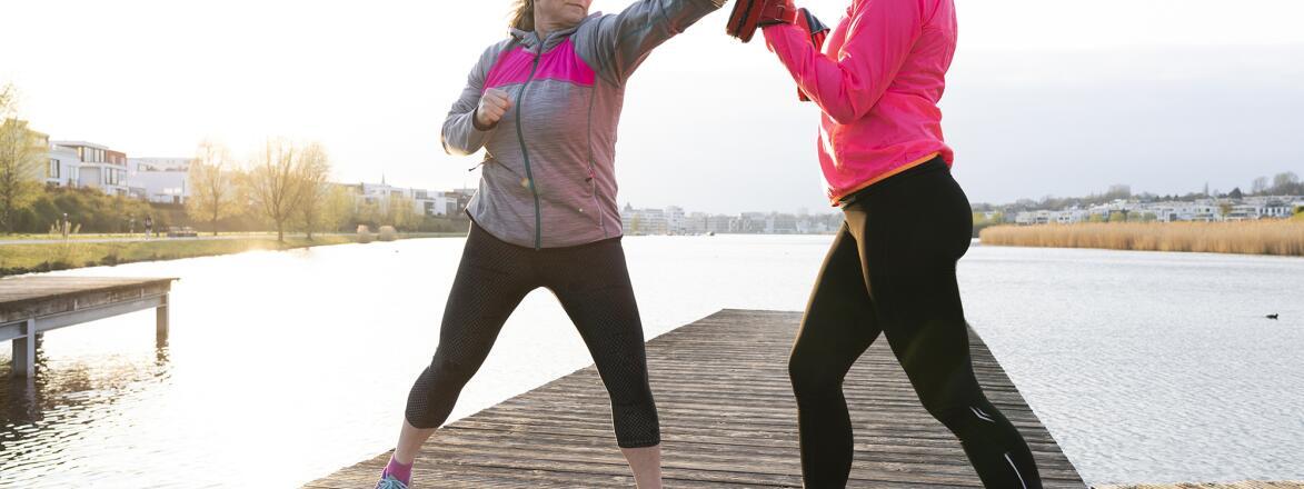 two women practicing self defense near a lake