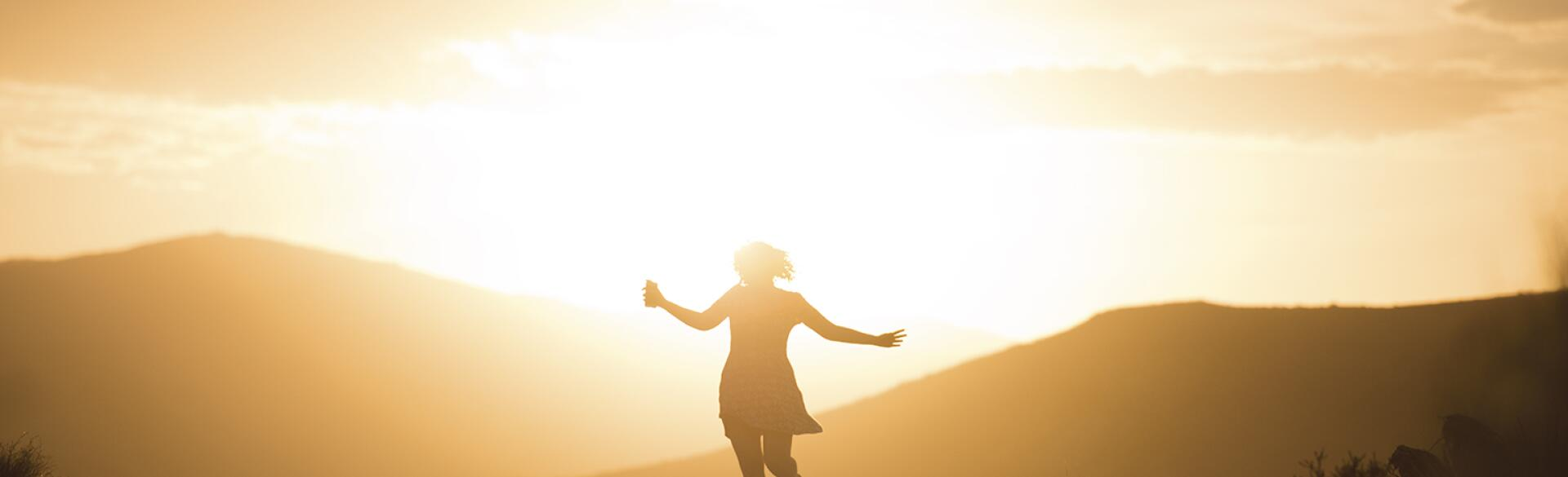 An image of a woman running carefree in the sunrise.