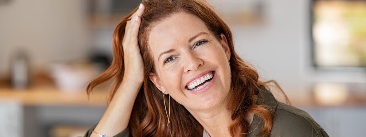 Woman with red hair looking at camera and smiling