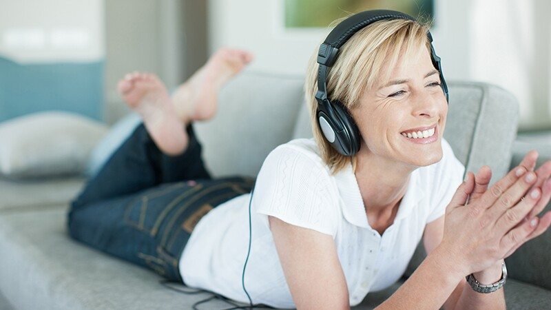 A woman with headphones on lying on the couch
