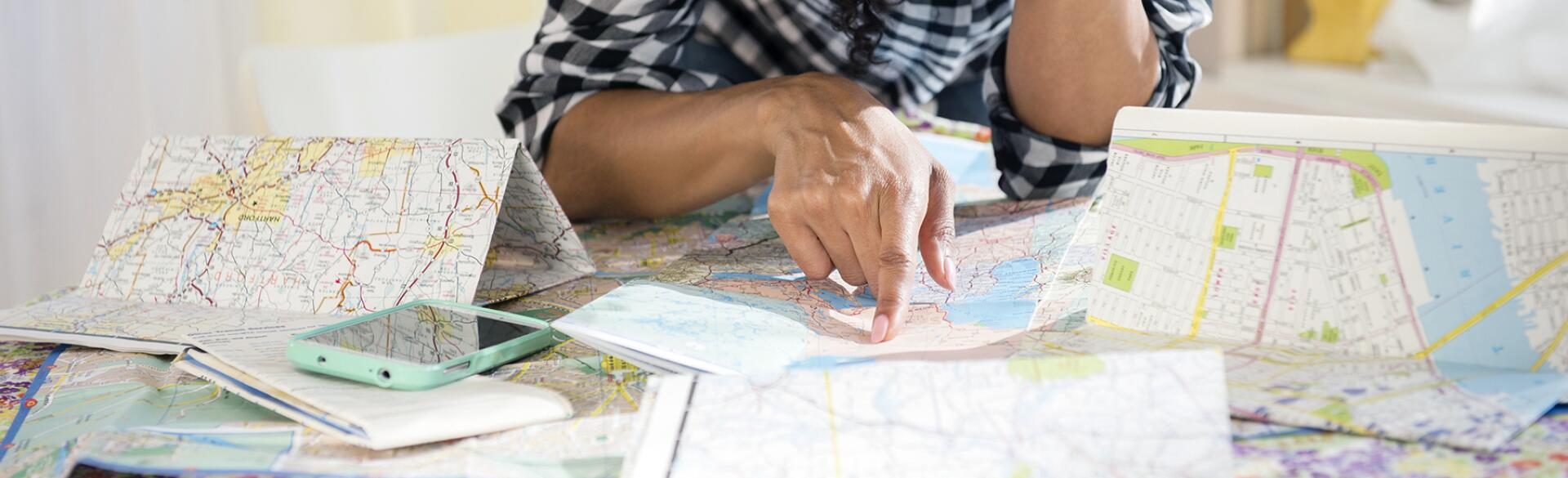 woman_looking_at_map_on_table_GettyImages-557475331_1800