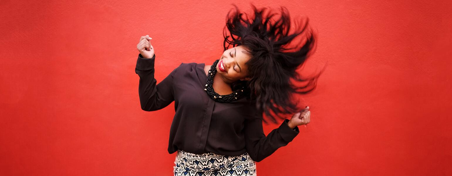 African American Woman Dancing on red background to cheer up