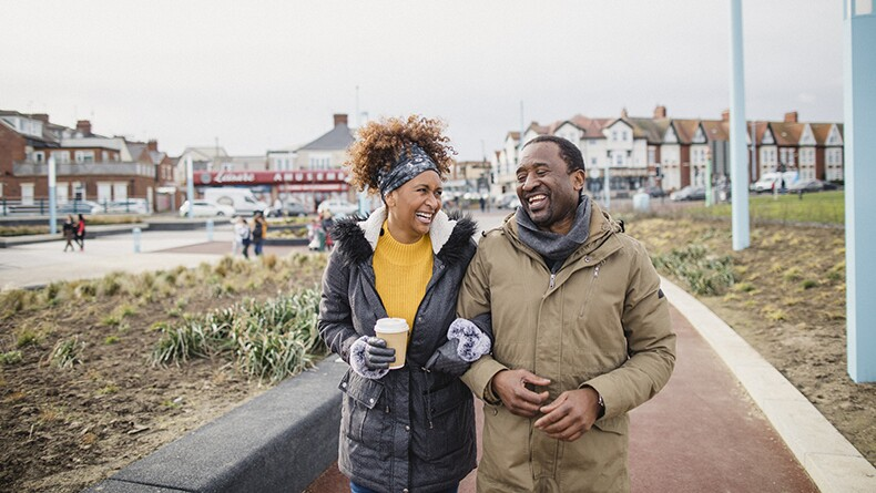 Black woman and man walk in neighborhood