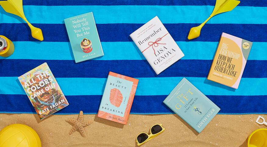 Six summer books laid out on a beach blanket