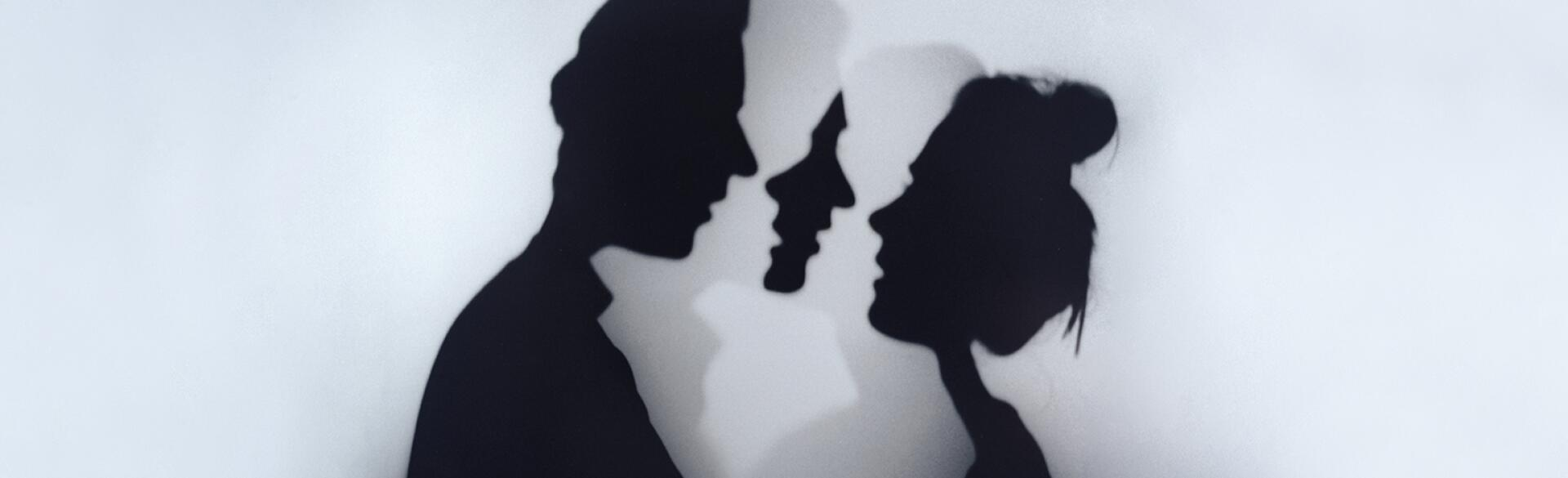 A photo of a woman and man standing face to face.