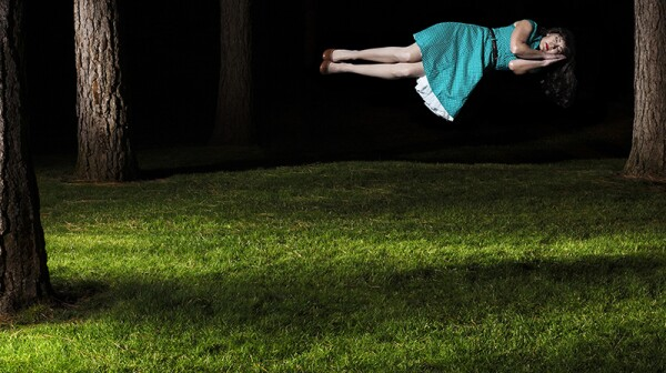 A woman floating in the air as she sleeps outside