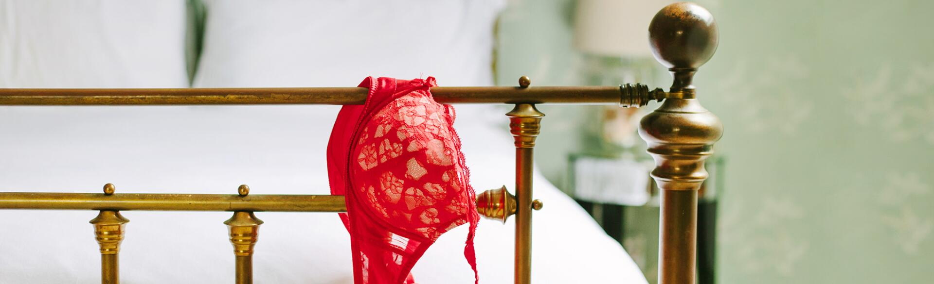 end of bed post with red bra hanging off the edge