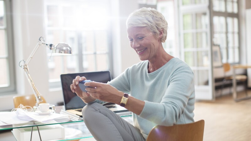 mature woman looking at phone while at her home desk