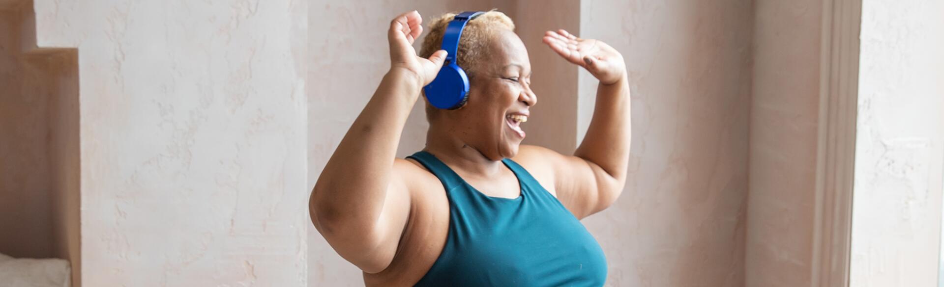 Older Black woman dancing with headphones on
