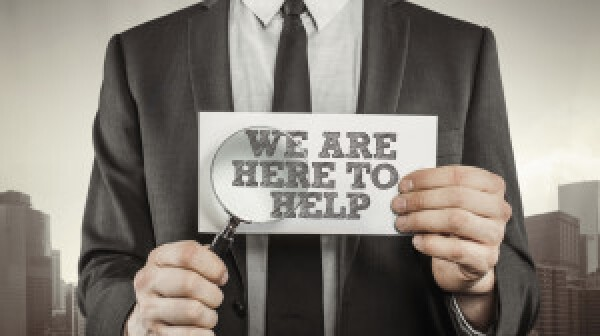 Man in suit holding 'We are here to help' sign
