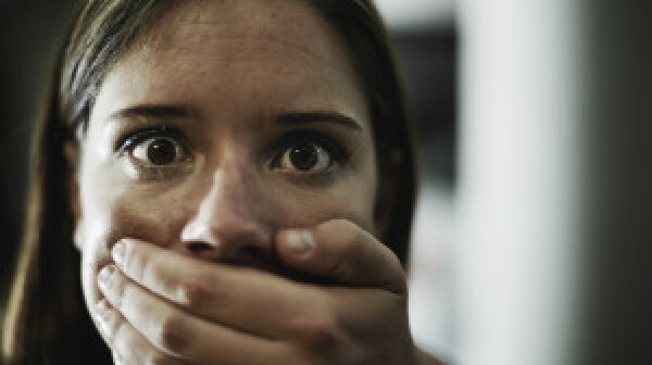 A terrified young woman held captive by a man with his hand over her mouth