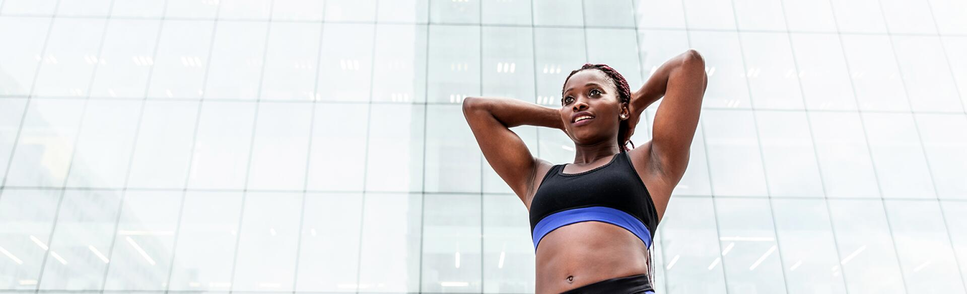 A photo of a woman in fitness gear, posing to show off her curves.
