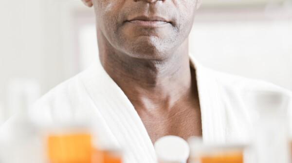 iStock_000012250489MedicineCabinet Black man holding pill bottle