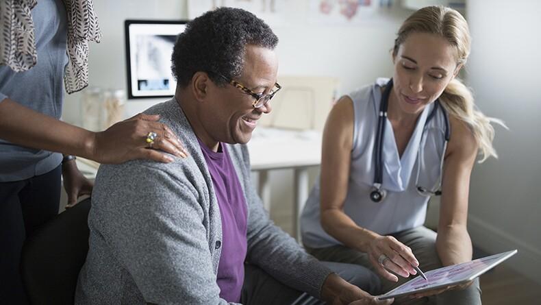 A blonde female doctor shows  an older black man a tablet during a medical visit.