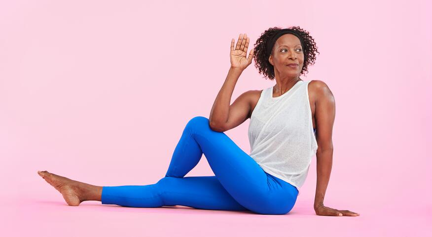 african american woman wearing athletic clothes stretching with yoga on a pink background