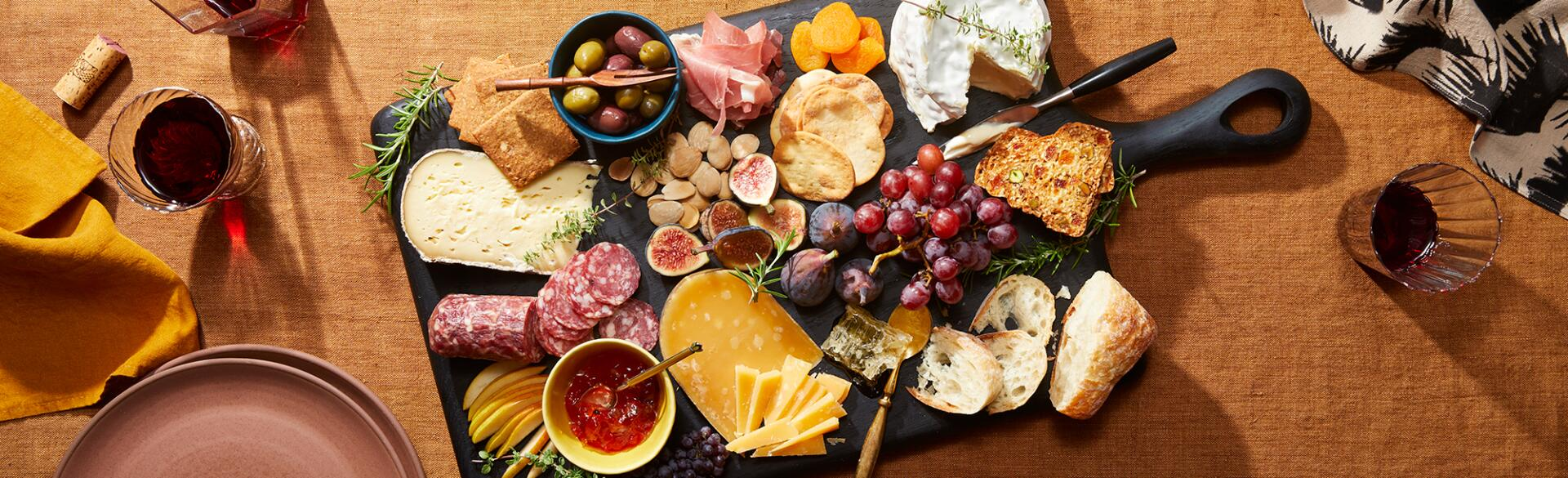 Charcuterie board with a display of cheese and meats on a rust colored table cloth, red wine, plates and napkins