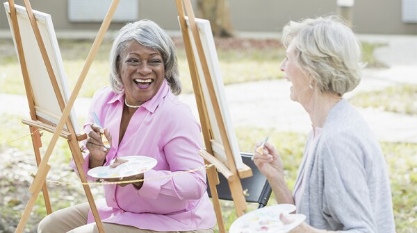 Two women smiling and laughing as they paint outdoors