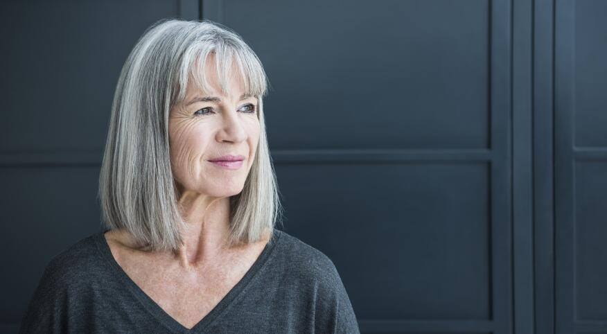 woman with gray hair looking off to camera