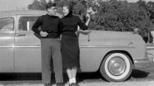 Old photo of couple leaning on car