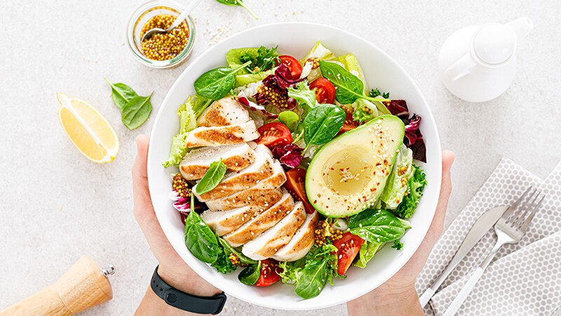An overhead view of grilled chicken meat and vegetable salad in a bowl