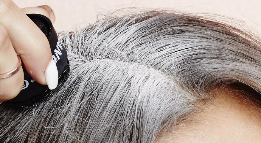 woman touching up her gray roots