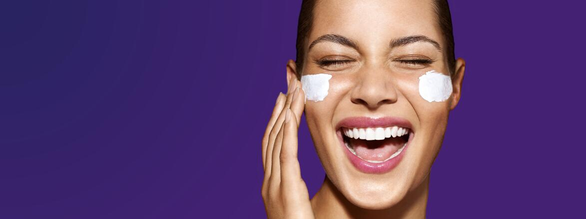woman smiling with eye cream under her eyes