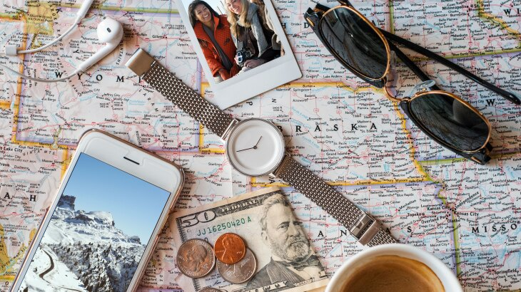 Photo of a U.S. map with miscellaneous travel items on top like a watch, sunglasses, headphones, money, cell phone and polaroid photo.