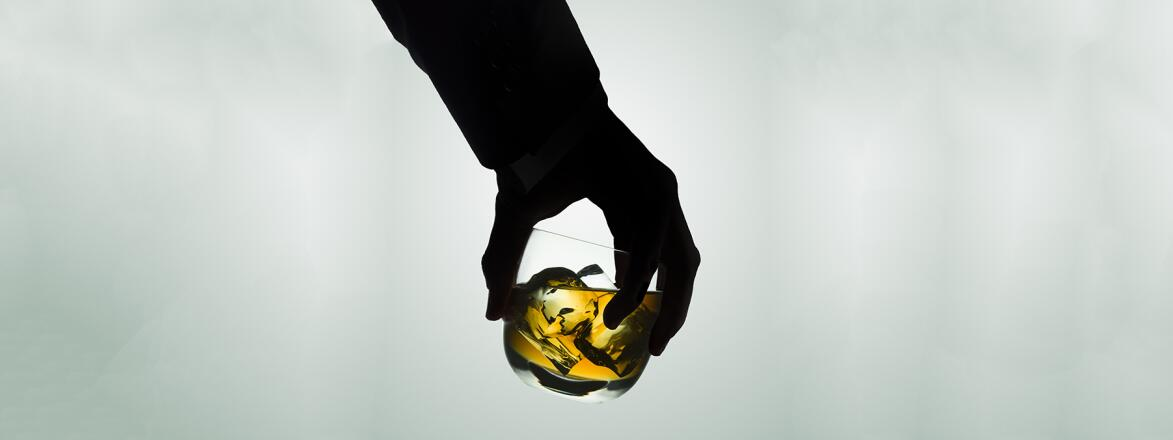 Silhouetted male hand holding a glass of whiskey