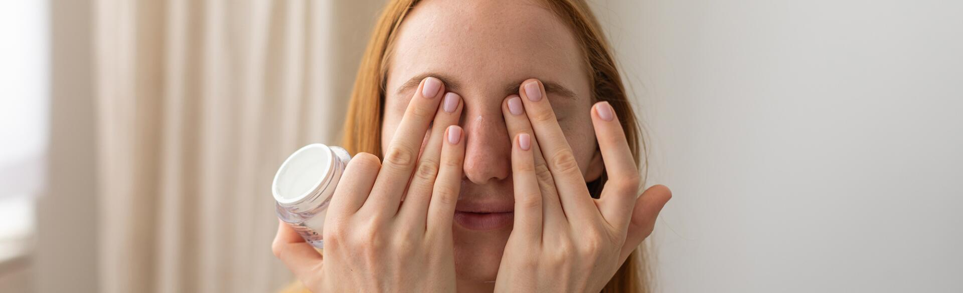 woman putting eye cream over her eyes at home