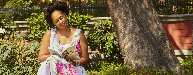 Shonda Buchanan sitting on a park bench reading her book titled Black Indian
