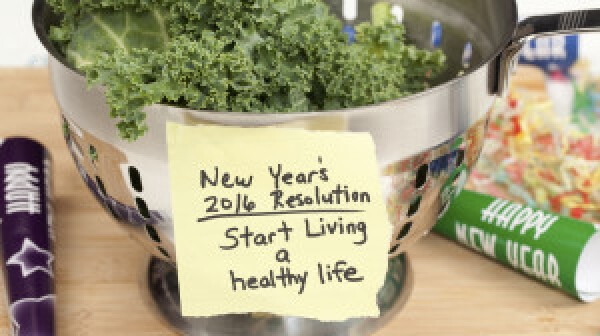 New Years 2016 resolution reminder note to start living a healthy lifestyle taped to a colander filled with fresh kale. Party horn blower and confetti add a festive feel to the image. Shot in studio with Canon 5D Mark II DSLR camera.