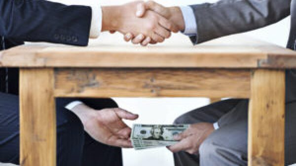 Two men in suits shaking hands while one takes cash