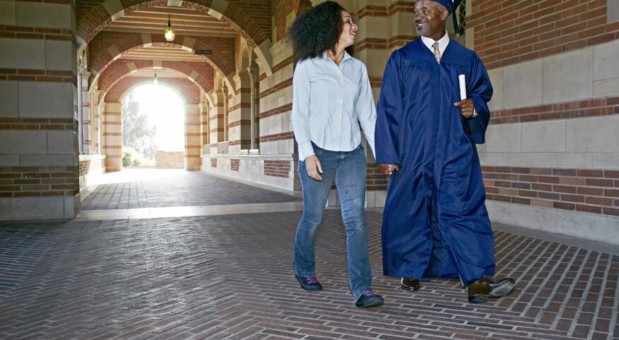 Daughter walking with father in graduation cap and gown